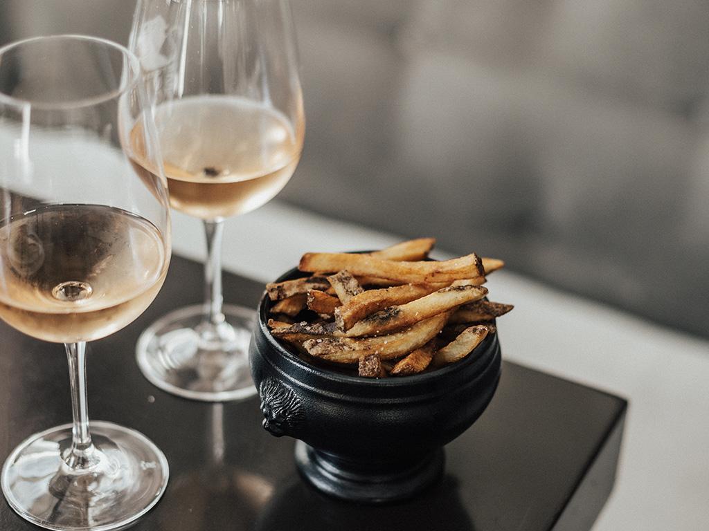 Deux verres de vin blanc et une assiette de frites sur une table