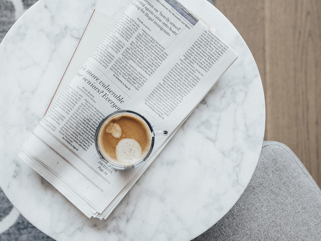 Une tasse de café et un journal posés sur une table